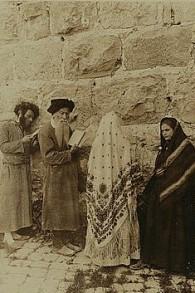 Deux hommes et deux femmes, tous Juifs, devant le pur Occidental de Jérusalem en 1908 environ (Crédit : Underwood & Underwood/Library of Congress)