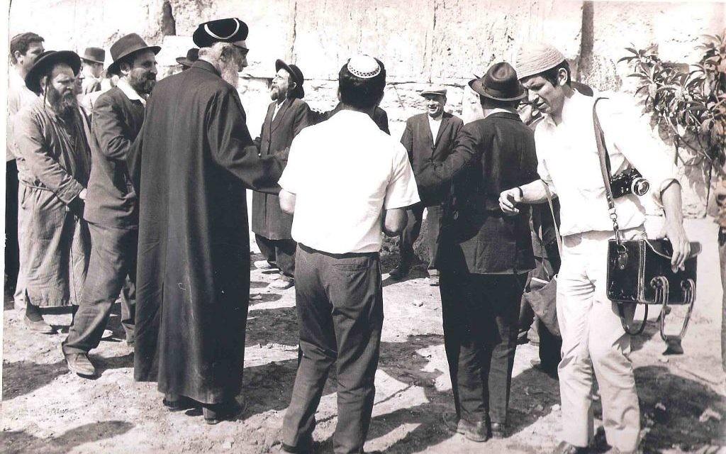 Le photoreporter Jacques Héripret, à droite, devant le mur Occidental avec ses appareils photo, le 6 juin 1967. (Crédit : Collection Jacques Héripret)