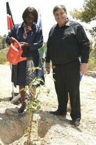La professeure Judi Wakhungu, ministre de l'Environnement et des Ressources naturelles au Kenya et le président du FNJ/KKL Danny Atar, plantent un caroubier près du mémorial Yad Kennedy, le 27 juin 2017. (Crédit :Avi Hiun, KKL-JNF)