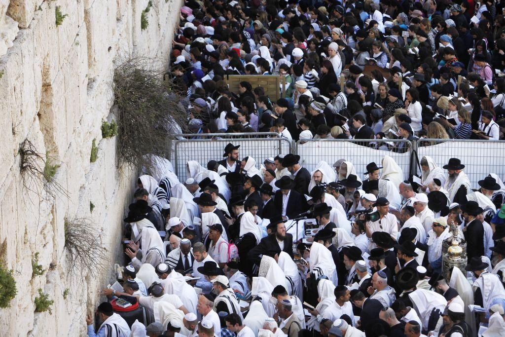 Des hommes Juifs et des femmes Juives prient devant le mur Occidental dans la vieille ville de Jérusalem, durant la bénédiction de Cohen lors de la fête juive de Pessah, le 9 avril 2012 (Crédit : Miriam Alster/Flash90)