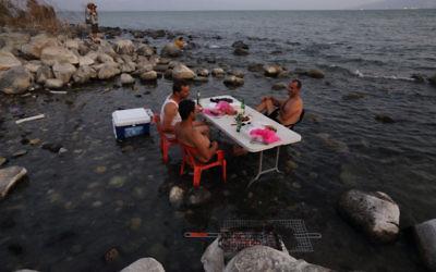 Des Israéliens au lac de Kinneret profitent d'un barbecue dans l'eau, le 18 août 2014 (Crédit : Yaakov Naumi/Flash90)