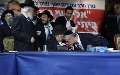 Le chef du parti Yachad Eli Yishai embrasse la main du rabbin Meir Mazuz lors d'une conférence de presse à Bnei Brak, le 25 décembre 2014 (Crédit : Yaakov Naumi / Flash90)