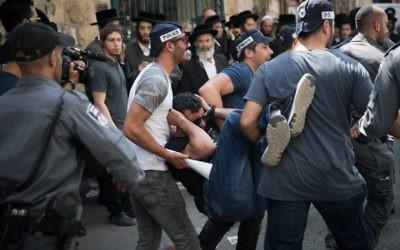 Des policiers israéliens transportant l'un de leur collègue blessé pendant une opération d'arrestation d'attaquants de soldats ultra-orthodoxes dans le quartier Mea Shearim de Jérusalem, le 4 juin 2017. (Crédit : Yonatan Sindel/Flash90)