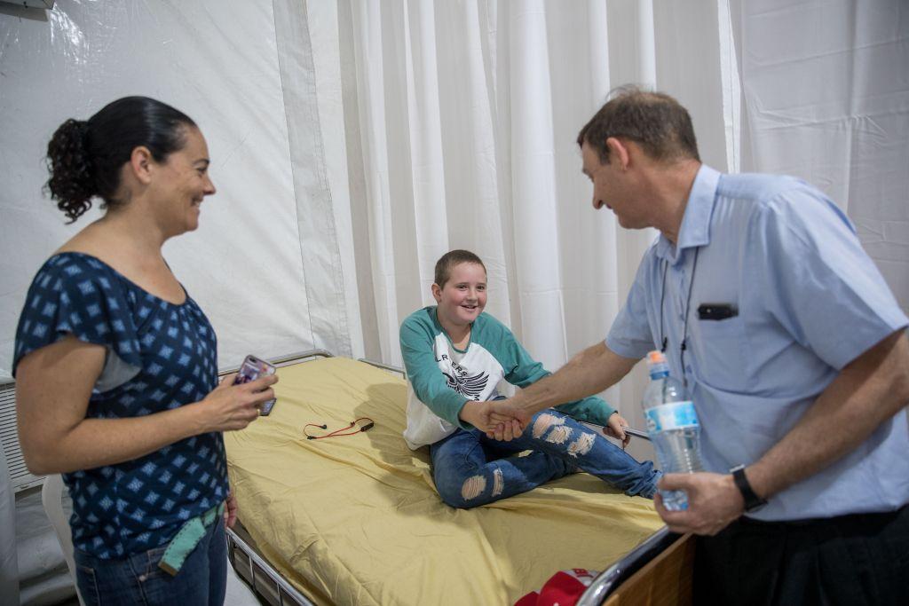 Le professeur Michael Weintraub avec un patient dans une tente de protestation installée dans le parc Sacher par des parents de jeunes enfants atteints d'un cancer et soignés dans le département d'onco-hématologie pédiatrique de l'hôpital Hadassah Ein Kerem, à Jérusalem, le 4 juin 2017. (Crédit : Yonatan Sindel/ Flash90)