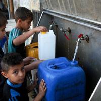 Des enfants palestiniens remplissent des jerrycans avec de l'eau potable provenant de robinets publics dans le sud de la bande de Gaza, le 11 juin 2017 (Crédit : Abed Rahim Khatib / Flash90)