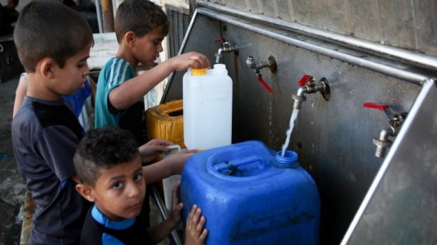 Les enfants palestiniens remplissent des jerrycans avec de l'eau potable provenant des robinets publics dans le sud de la bande de Gaza, le 11 juin 2017 (Crédit : Abed Rahim Khatib / Flash90)