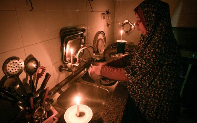 Une femme palestinienne fait la vaisselle à la lumière de la chandelle dans le camp de réfugiés de Rafah, dans le sud de la bande de Gaza, le 12 juin 2017. (Crédit : Abed Rahim Khatib/Flash90)