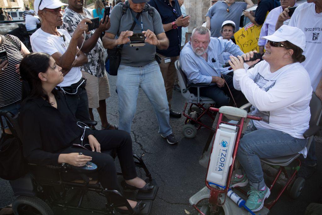 Les députés Karin Elharar, à gauche, et Ilan Gillon, deuxième à droite, pendant une manifestation contre la hausse insuffisante de l'allocation handicapé, devant la résidence du Premier ministre à Jérusalem, le 27 juin 2017. (Crédit : Yonatan Sindel/Flash90)