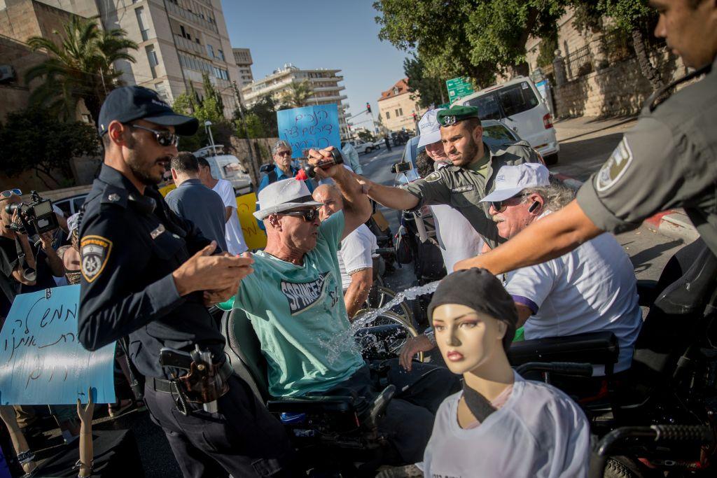 Un militant tentant de s'immoler pendant une manifestation contre la hausse insuffisante de l'allocation handicapé, devant la résidence du Premier ministre à Jérusalem, le 27 juin 2017. (Crédit : Yonatan Sindel/Flash90)