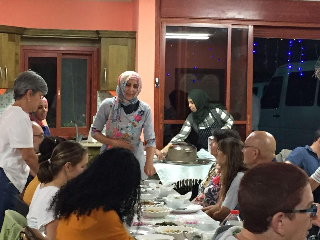 La propriétaire d'un restaurant, Manal Karaman, décrit aux participants de la visite des Nuits du Ramadan les plats qu'elle a préparé pour la rupture du jeûne, le 22 juin 2017 (Crédit : Amanda Borschel-Dan/Times of Israel)