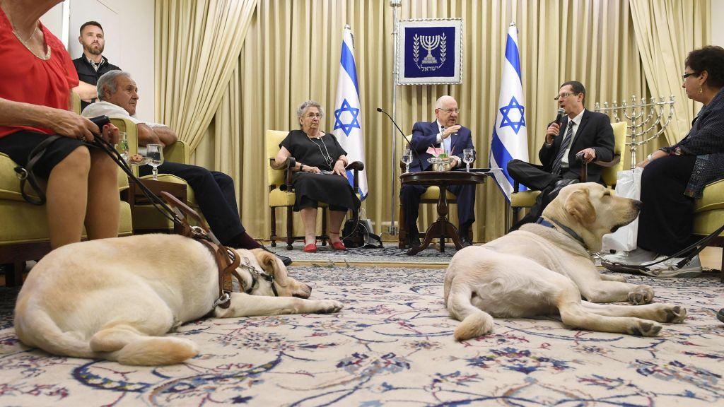 Le président israélien Reuven Rivlin et son épouse accueillent des personnes malvoyantes en l'honneur de la Journée mondiale des aveugles et des malvoyants à la résidence présidentielle, le 6 juin 2017 (Crédit : Mark Neyman/GPO)