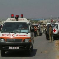 Des membres de la Croix Rouge internationale effectuent le transport de Palestiniens malades depuis Gaza vers Israël au poste frontière Erez, le 19 juin 2007. (Crédit : Ahmad Khateib/ Flash90)
