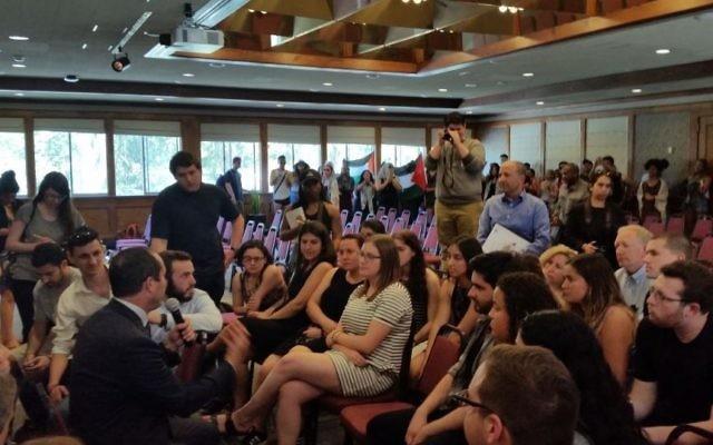 Le maire de Jérusalem Nir Barkat s'adresse à des étudiants de l'université de San Francisco le 6 avril 2016, alors que des manifestants pro-palestiniens protestent dans le fond de la salle (Crédit : Municipalité de Jérusalem)