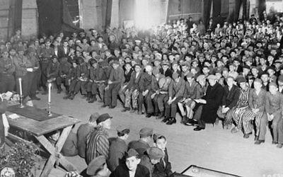 Le rabbin Herschel Schachter menant des services pour les survivants de l'Holocauste lors de la fête juive de Shavuot, dans le camp de concentration de Buchenwald, le 16 mai 1945 (Crédit : Wikimedia Commons)