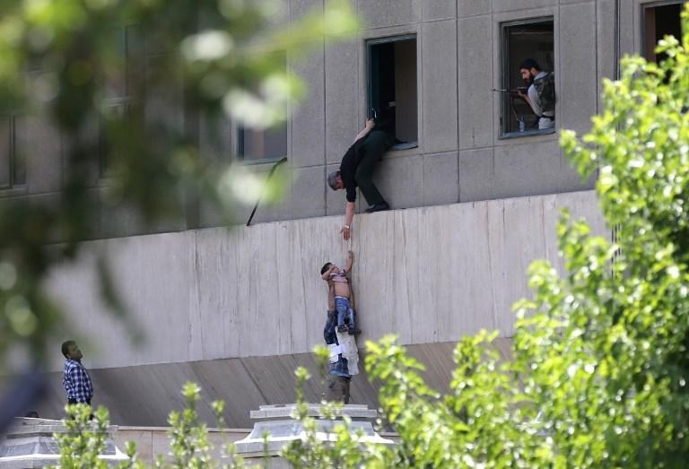 Des policiers iraniens évacuent un enfant du parlement de Téhéran pendant un attentat revendiqué par le groupe Etat islamique, le 7 juin 2017. (Crédit : Omid Vahabzadeh/Fars News/AFP)
