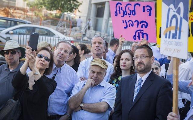 Natan Sharansky,  au centre, président de l'Agence juive, et Dov Lipman, alors député, en costume cravate à droite, lors d'une manifestation organisée par les Juifs orthodoxes américains et israéliens et les Juifs conservateurs devant les bureaux du grand-rabbinat à Jérusalem, le 6 juillet 2016 (Crédit : Hadas Parush/Flash90)