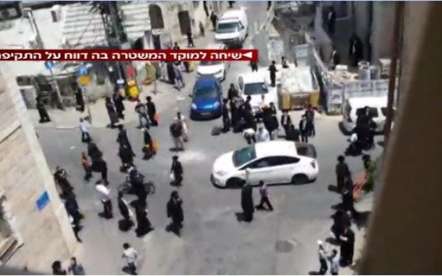 Des hommes ultra-orthodoxes s'en prennent à un soldat en uniforme, dans le quartier de Mea Shearim à Jérusalem, le 9 juin 2017. (Crédit : capture d'écran la Deuxième chaîne)