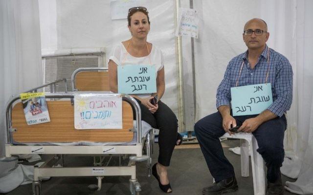 """Shlomo Ben Dor, à droite, et Pazit Ben Israel dans la tente de protestation montée par les parents des patients du service d'onco-hématologie pédiatrique dans le parc Sacher de Jérusalem, portant des panneaux indiquant """"Je suis en grève de la faim"""", le 25 juin 2017. (Crédit : Yonatan Sindel/Flash90)"""