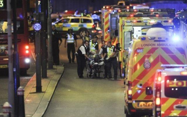 Des policiers et membres des services d'urgence s'occupent des blessés lors de l'attaque terroriste sur le London Brigde, le 2 juin 2017. (Crédit : AFP Photo / Daniel Sorabji)