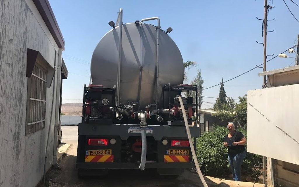 Yael Hashash, directrice de l'implantation de Migdalim contemple la citerne qui approvisionne son implantation en eau, le 4 juin 2017. (Crédit : Jacob Magid/Times of Israel)