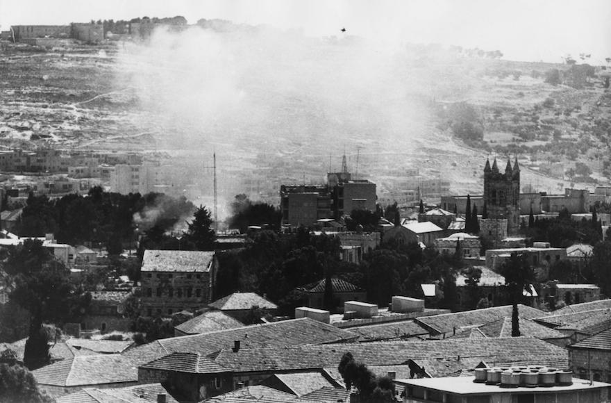 De la fumée émane de la Vieille ville de Jérusalem pendant la guerre des Six jours, en juin 1967. (Crédit : Keystone/Hulton Archive/Getty Images)