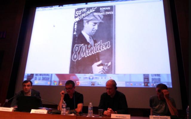 Conférence sur le polar allemand au Mémorial de la Shoah. A gauche, le spécialiste du genre, Vincent Platini. En fond, un polar publié par Michael Zwick, un auteur juif, durant le IIIe Reich (Crédit : capture d'écran Facebook/Onirik)