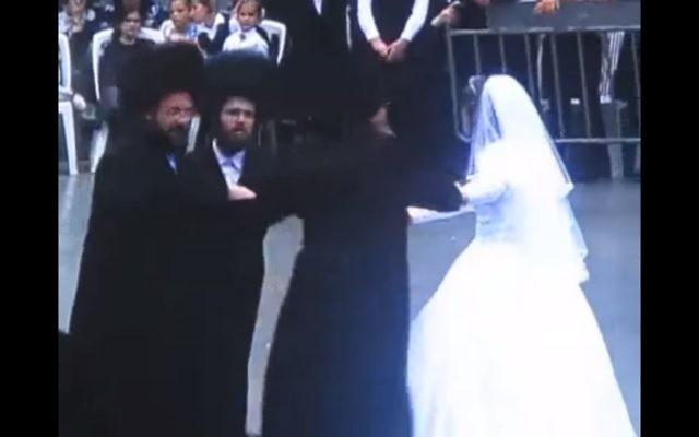Le rabbin de Karlin-Stolin au mariage de sa fille. Il danse avec sa fille, le jeune marié et son père, à Tel Aviv le 25 juin 2017. (Crédit : capture d'écran YouTube)