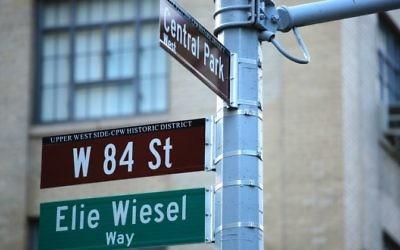 Nom des rues au coin de la 84e rue et de Central Park West à New York, qui porte maintenant le nom d'Elie Wiesel, survivant de la Shoah, écrivain et prix Nobel de la Paix, à New York, le 13 juin 2017. (Crédit : Kena Betancur/AFP)