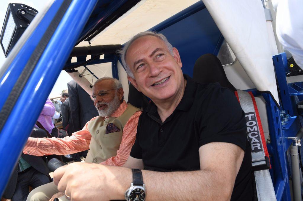 Le Premier ministre Benjamin Netanyahu, à droite, et son homologue indien Narendra Modi dans un buggy qui purifie de l'eau en roulant, sur la plage Olga, le 6 juillet 2017. (Crédit : Kobi Gideon/GPO)