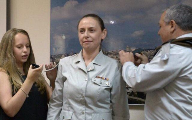 Le brigadier-général de l'armée israélienne Ariella Lazrovitch reçoit son nouveau grade du chef d'Etat major de l'armée israélienne Gadi Eiesnkot et de sa fille, ainsi que son nouveau poste de conseillère économique en chef de l'armée le 27 juillet  2017. (Crédit : Unité du porte-parole de l'armée IDF )