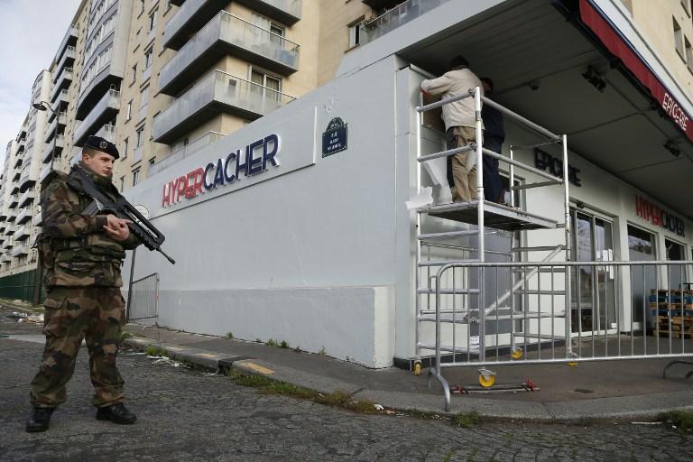 Un soldat français monte la garde alors qu'un employé municipal pose une plaque commémorative devant le supermarché juif Hyper Cacher à Paris, le 4 janvier 2016, en mémoire des quatre personnes tuées durant un attentat terroriste dans le magasin le 9 janvier 2015 (Crédit : Thomas Samson/AFP)