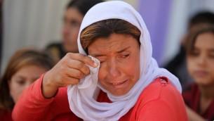 Une femme yézidie irakienne déplacée s'essuie les yeux dans le camp de Bajid Kandala situé à proximité du Tigre, dans la province occidentale de Dohuk au Kurdistan, où elle s'est réfugiée après avoir fui l'avancée des djihadistes de l'EI en Irak, le 13 août 2014 (Crédit ::AHMAD AL-RUBAYE/AFP)
