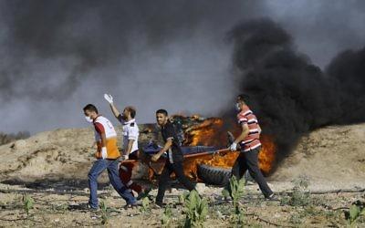 Manifestants et secouristes palestiniens transportent un blessé pendant des affrontements contre les forces de sécurité israéliennes à la frontière gazaouie, à l'est du camp de réfugiés de Jabalia, le 23 juin 2017. (Crédit : Mohammed Abed/AFP)