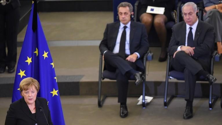 La chancelière allemande Angela Merkel prononce un discours durant les funérailles du défunt chancelier Helmut Kohl. Au premier rang, l'ancien président français Nicolas Sarkozy et le Premier ministre israélien Benjamin Netanyahu, au Parlement européen à Strasbourg, le 1er juillet 2017. (Crédit : AFP PHOTO/Patrick HERTZOG)