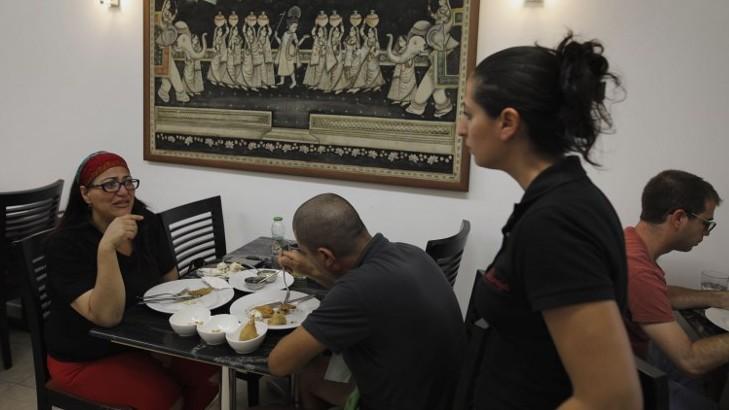 Des israéliens mangent dans le restaurant indien Maharaja, à Ramla, au sud de Tel Aviv, le 2 juillet 2017, alors que la communauté juive indienne se prépare à l'arrivée du Premier ministre indien en Israël .(Crédit : AFP/ MENAHEM KAHANA)