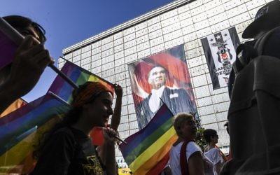 Des activistes LGBTQ brandissent des drapeaux pendant qu'ils défilent, le 2 juillet 2014, à Istanbul, en dépit de l'interdiction du gouvernement. (Crédit : AFP / BULENT KILIC)