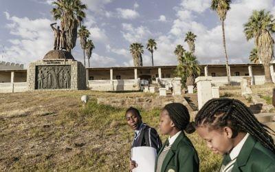 Des écolières namibiennes passent devant le mémorial construit en hommage aux victimes du prétendu génocide commis par les forces allemandes des tribus Herero et Nama en 1904, le 20 juin 2017 à Windhoek, en Namibie (Crédit : AFP PHOTO / GIANLUIGI GUERCIA)