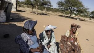 Des femmes âgées Herero : Sarafia Komomungondo (au centre), Lidya (à gauche) et Veronique Mujazu (à droite) en dehors de leurs maisons dans la périphérie de la ville appauvrie d'Okakarara le 22 juin 2017 à Okakarara, en Namibie (Crédit : AFP PHOTO / GIANLUIGI GUERCIA)