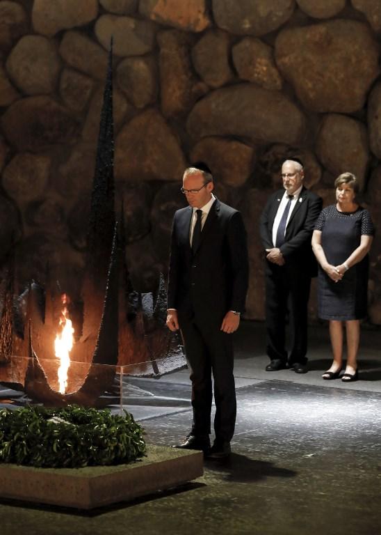 Le ministre irlandais des Affaires étrangères Simon Coveney dépose une gerbe dans la Salle des noms, où les noms des camps de la mort et de concentration sont écrits, durant une visite au musée du mémorial de l'Holocauste Yad Vashem qui commémore les six millions de Juifs assassinés par les nazis durant la Deuxième guerre mondiale, à Jérusalem, le 11 juillet 2017 (Crédit : GALI TIBBON/AFP PHOTO)