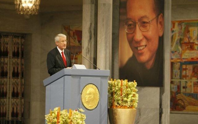 (Archives) Photo prise le 10 décembre 2010. Le président de la Commission Nobel Thorbjorn Jagland lors d'une cérémonie à Oslo devant la photo du lauréat du prix Nobel de la Paix,  Liu Xiaobo, décédé le 13 juillet 2017. (Crédit : AFP PHOTO / NTB Scanpix / Heiko JUNGE / Norway OUT)