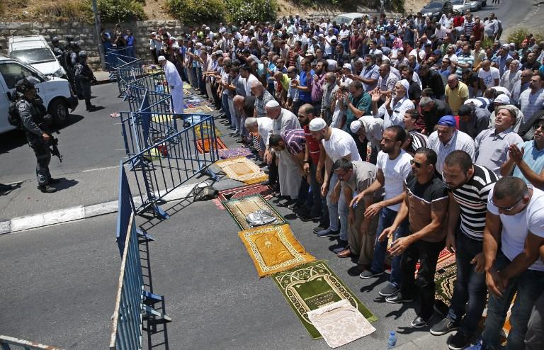 Les fidèles musulmans prient dans une rue aux abords de la porte des Lions, à proximité du mont du Temple, le 14 juillet 2017, après que trois terroristes israéliens arabes ont tué deux agents de police  (Crédit :  AHMAD GHARABLI/AFP PHOTO)