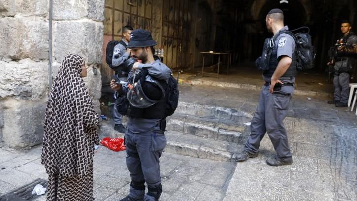 Un garde-frontière israélien regarde la carte d'identité d'une femme musulmane dans la Vieille Ville de Jérusalem, le 16 juillet 2017. (Crédit : Menahem Kahana/AFP)