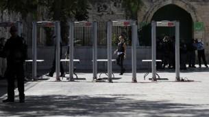 Des policiers israéliens installent des détecteurs de métaux aux abords de la Porte du Lion, entrée principale du mont du Temple, dans la Vieille ville de Jérusalem, après que les forces de sécurité ont rouvert ce lieu ultra-sensible qui avait été fermé après une attaque meurtrière la semaine dernière, suscitant la colère. Photo prise le 17 juillet 2017 (Crédit : AHMAD GHARABLI/AFP)