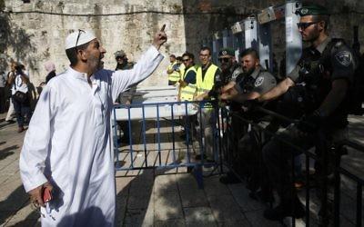 Un Palestinien interpelle les garde-frontières israéliens se tenant à côté des nouveaux détecteurs de métaux à l'entrée principale du mont du Temple dans la Vieille ville de Jérusalem, le 16 juillet 2017, après la réouverture de ce site ultra-sensible (Crédit :  AHMAD GHARABLI/AFP PHOTO)