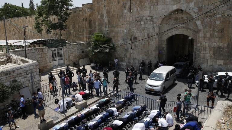Des fidèles musulmans prient aux abords de la Vieille ville de Jérusalem en protestation contre l'installation de détecteurs de métaux aux entrées du mont du Temple, le 17 juillet 2017 (Crédit : Ahmad Gharabli/AFP PHOTO)