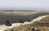 Des véhicules de l'armée israélienne le long de la route parallèle à la barrière de sécurité séparant les régions israélienne et syrienne du plateau du Golan, le 19 juillet 2017. (Crédit : Menahem Kahana/AFP)