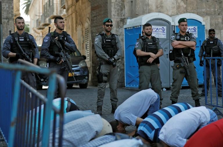 Les forces de sécurité israéliennes devant les fidèles palestiniens musulmans qui prient aux abords de la Porte des Lions, l'une des entrées principales vers le complexe du mont du Temple de la Vieille ville de Jérusalem, le 19 juillet 2017 (Crédit : Ahmad GHARABLI/AFP PHOTOS)