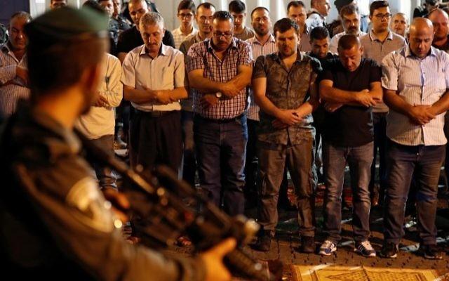 Fidèles musulmans devant la porte des Lions, à l'entrée du mont du Temple, dans la Vieille Ville de Jérusalem, le 19 juillet 2017. (Crédit : Ahmad Gharabli/AFP)