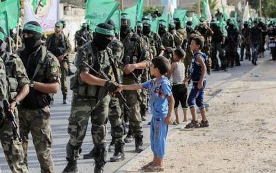 Des enfants palestiniens saluent les combattants des brigades Ezzedine al-Qassam, l'aile armée du groupe terroriste du Hamas dans les rues de la ville de Khan Yunis, dans le sud de la bande de Gaza, le 20 juillet 2017 (Crédit :  SAID KHATIB/AFP PHOTO)