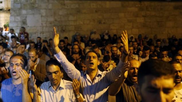 Des fidèles palestiniens musulmans prient aux abords de la porte des Lions, entrée principale au complexe du mont du Temple dans la Vieille ville de Jérusalem, le 20 juillet 2017 (Crédit : Ahmad GHARABLI/AFP PHOTO)